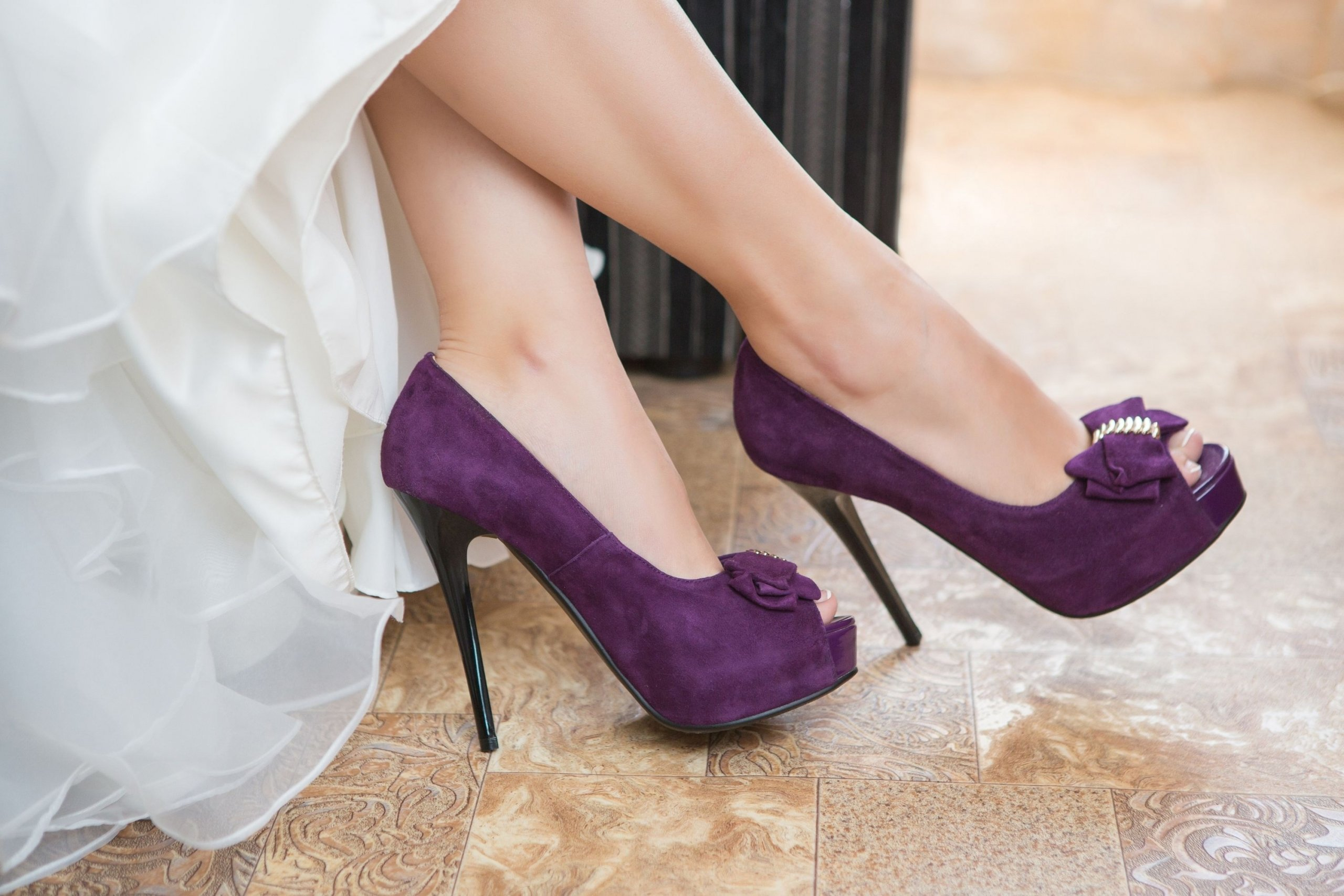 A woman's feet in purple open-toed high heel shoes