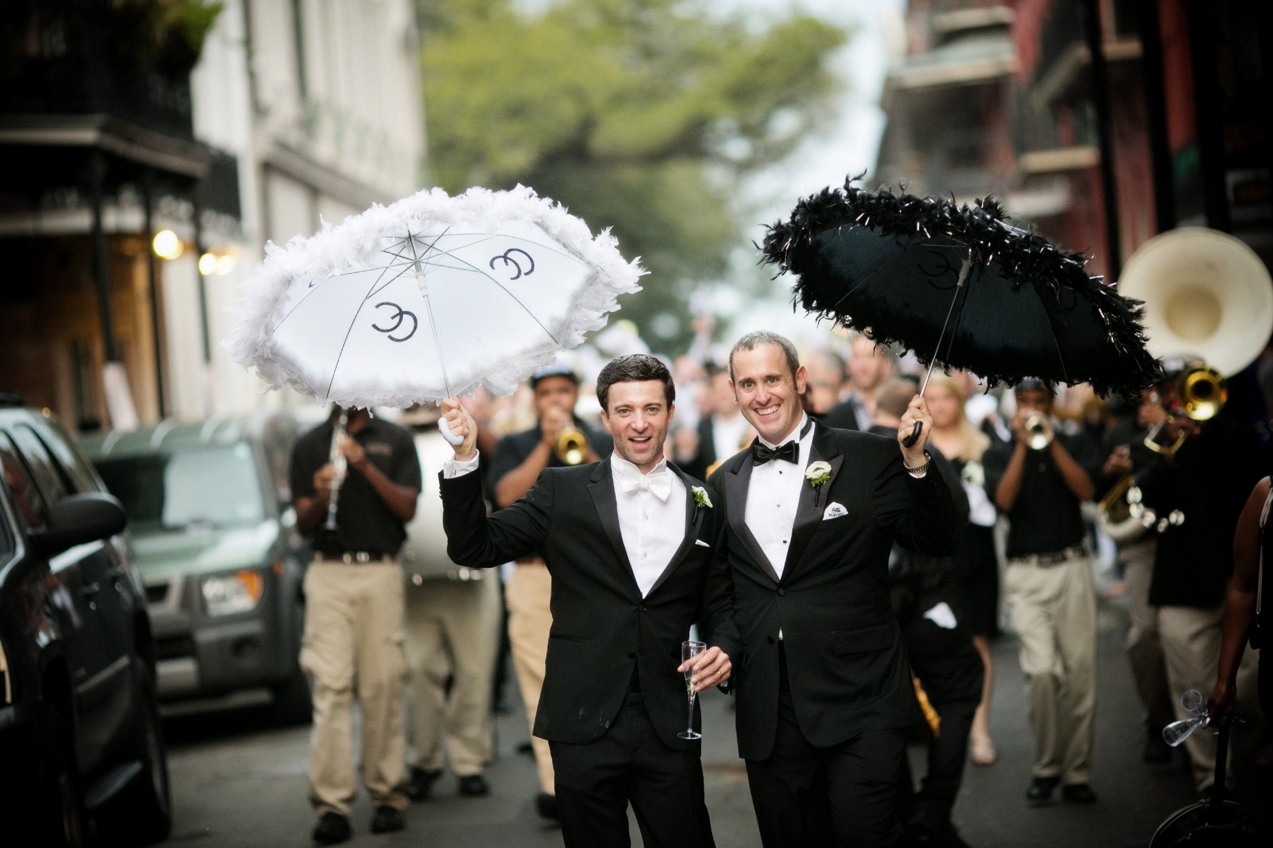 Two men in tuxedos in front of a New Orleans second line