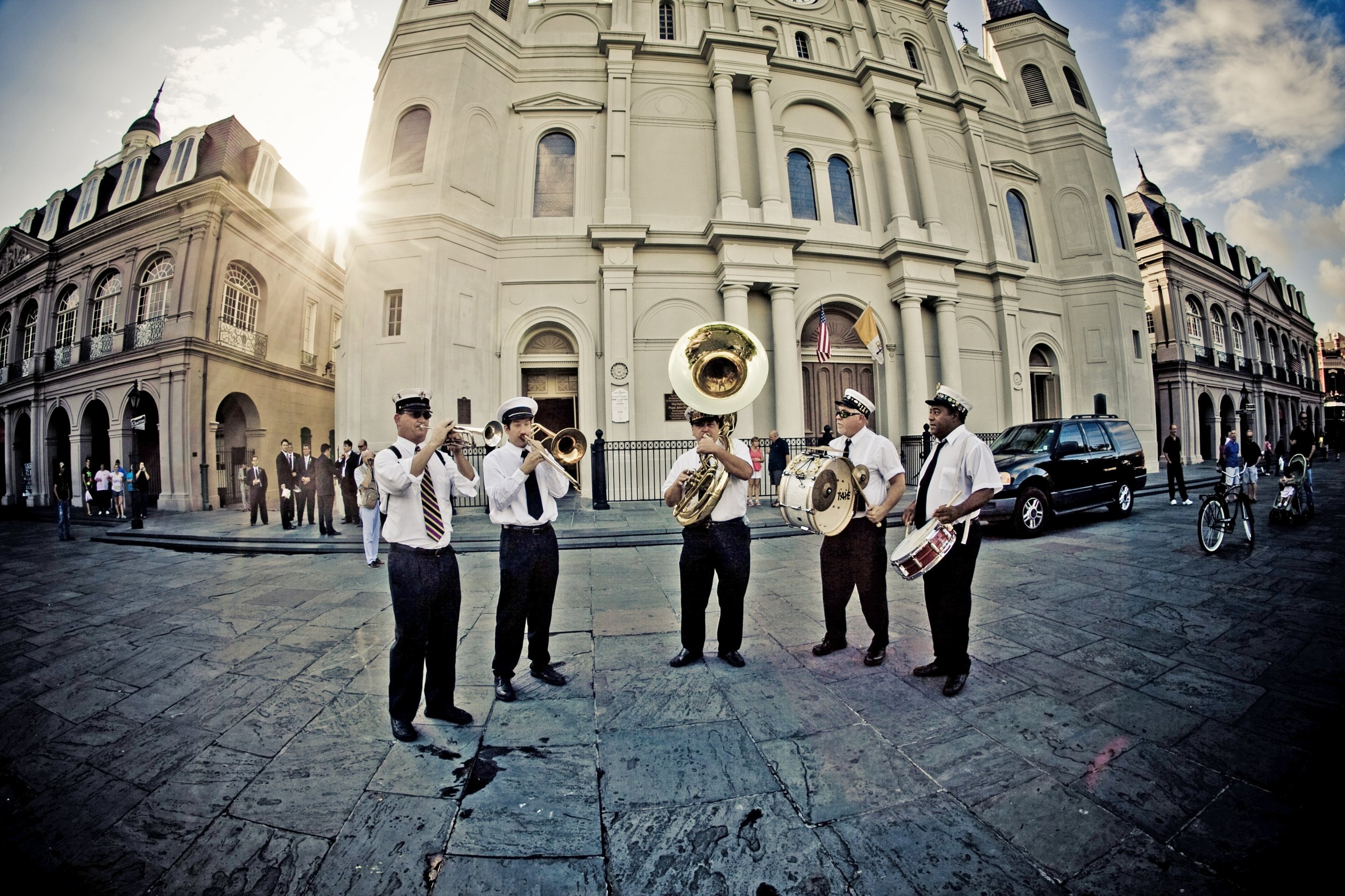 Five men playing instruments in a public square