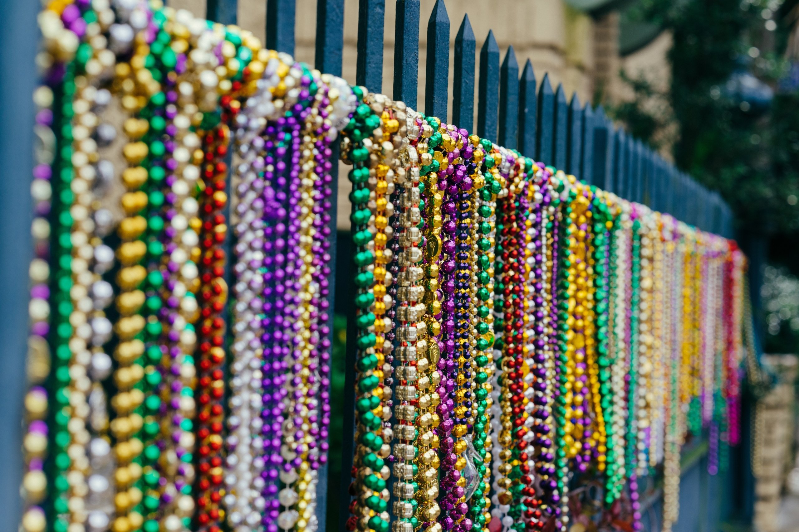 Colorful mardi gras beads tied to a blue fence