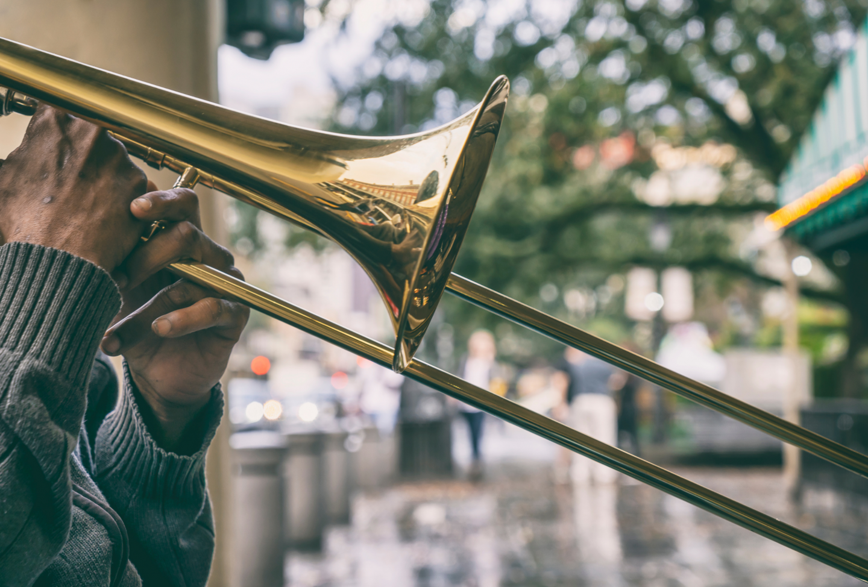 A man's hands holding a trombone