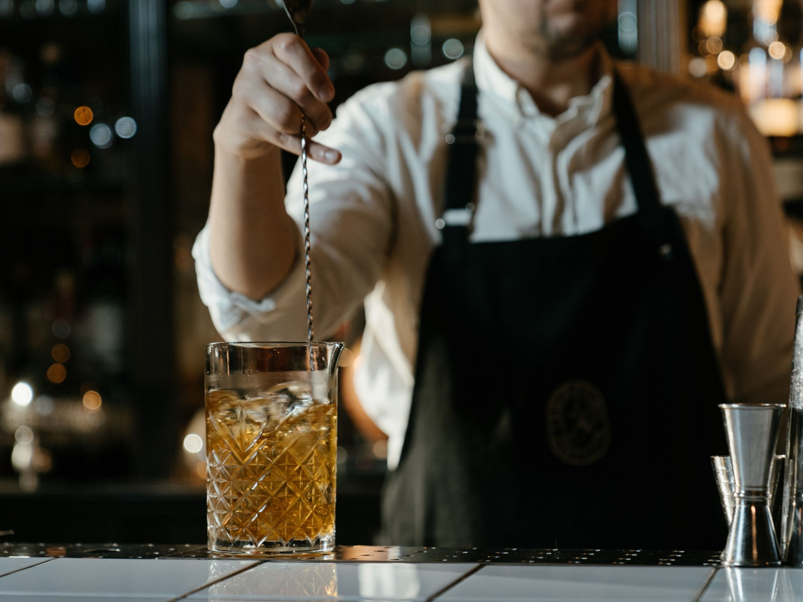 A hand mixing a drink with a mixing spoon on the bar counter