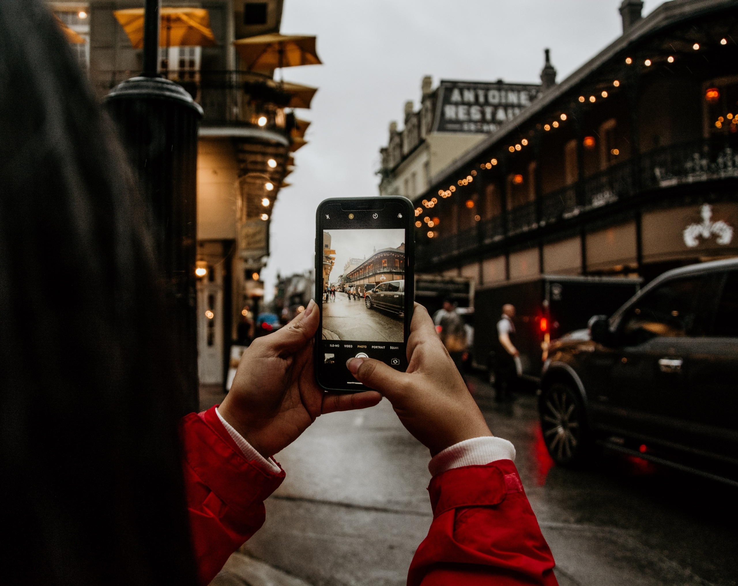 A woman taking a photo of Antoine's Restaurant with her phone
